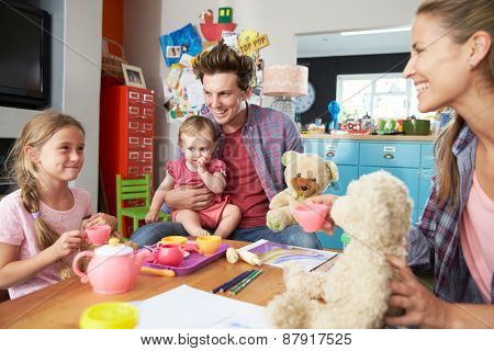 Parents Playing Game With Children And Toys In Bedroom