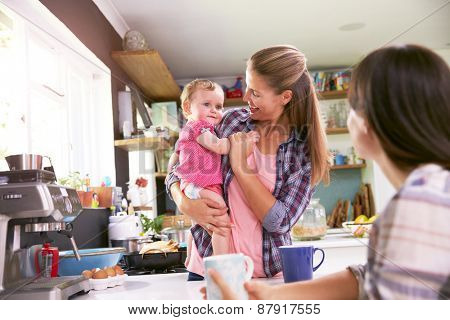 Mother With Young Daughter Talking To Friend In Kitchen