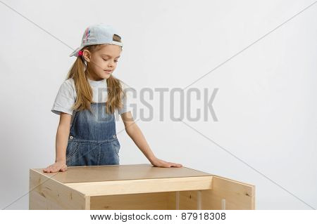 Child Looks At The Result Of Assembling Furniture