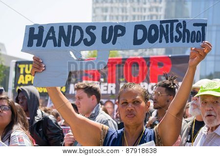 Woman Raising A Sign In The Form Of A Gun