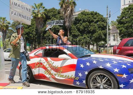 People Holding Sign Next To A Car Painted In American Flag Colors