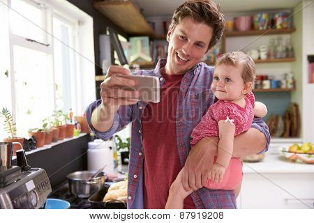 Father Cooks Meal Whilst Holding Young Daughter
