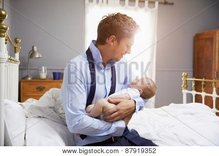 Father Dressed For Work Holding Baby In Bedroom