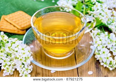 Tea in cup with cookies and flowers of bird cherry on board