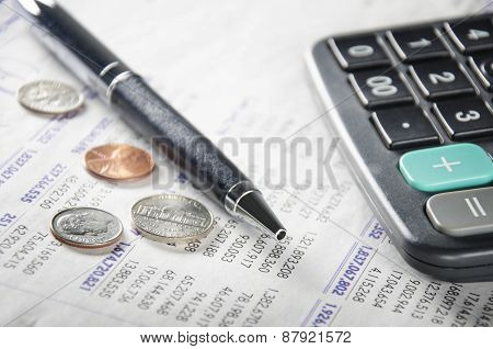 Calculator, pen, coins, and paper