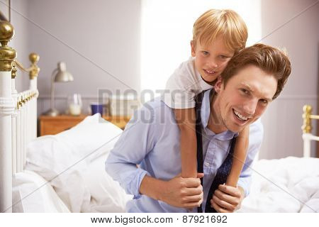Son Hugging Father As He Gets Dressed For Work