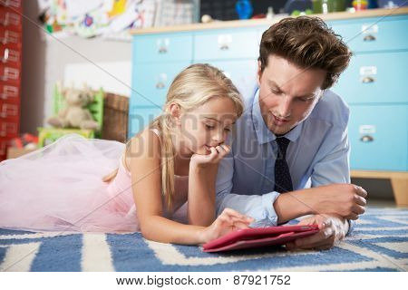 Father And Daughter Playing In Bedroom With Digital Tablet