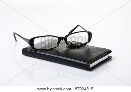 A Black notebook on top a glasses