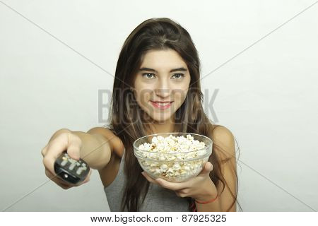 Young woman watching a movie with remote control.