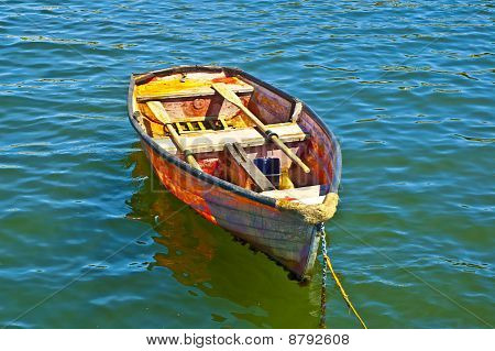 Paint Splattered Rowboat at Anchor on a Flat Sea