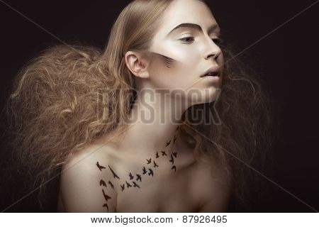 Beautiful girl with a pattern on the body in the form of birds, creative makeup and hairstyle lush.