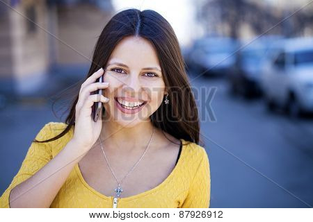 Young beautiful woman calls on his cell phone on the street