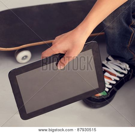 teenager sitting on box with tablet pc