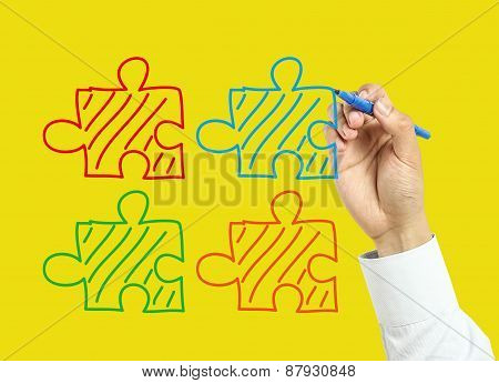 Businessman Hand Drawing Puzzles