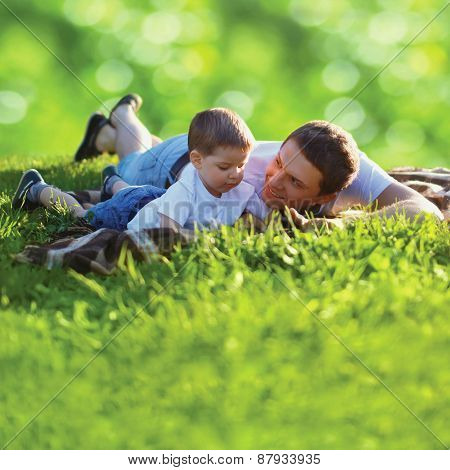Summer Photo Happy Father And Son Together Lying On Fresh Green Grass, Life Moment Family Resting On