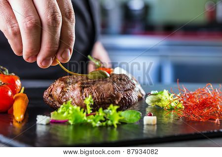 Chef in hotel or restaurant kitchen cooking, only hands. Prepared beef steak with vegetable decorati