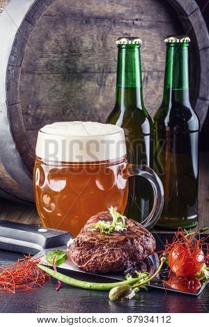 Beef steak withvegetable decoration. Beer barrel with beer glass and bottle