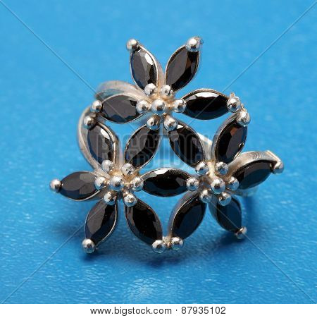 Silver Ring With Black Stones On A Blue Background