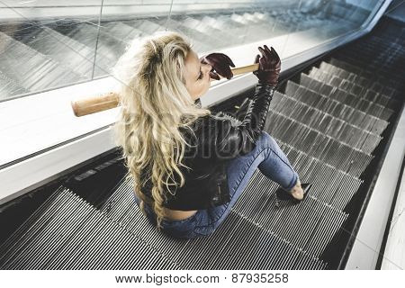 Urban beautiful blonde with a baseball bat in escalators