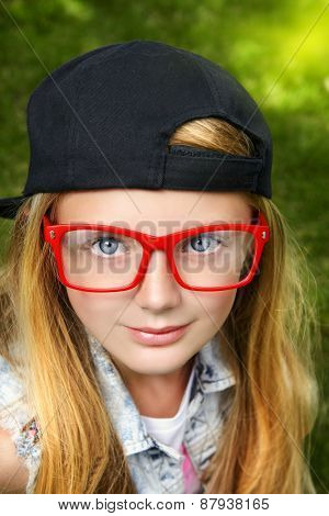 Close-up portrait of a pretty modern girl teenager wearing cap and spectacles.