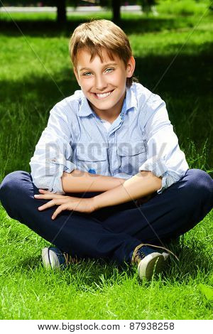 Cute boy sitting on a grass at a park and smiles. Summer day. Holiday.