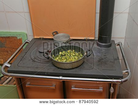 Pan With Zucchini Baked In Cast Iron Stove With Fire Lit