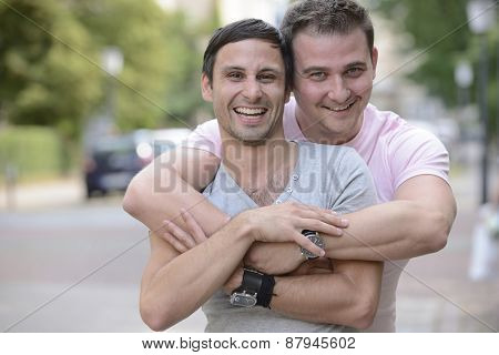 Happy gay couple outdoors hugging and smiling