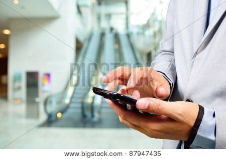 Business Man Using Mobile While Going Down Escalator