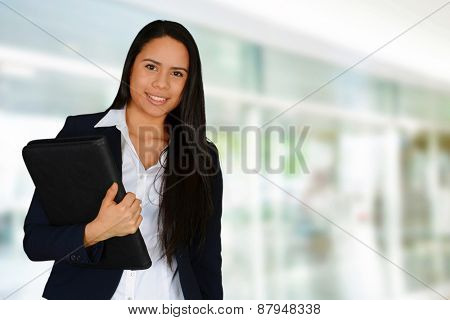 Young brunette holding file holder and looking at camera