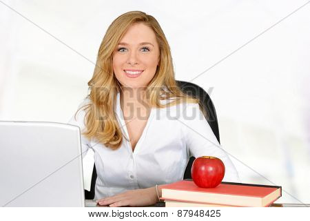Young teacher with red apple sitting