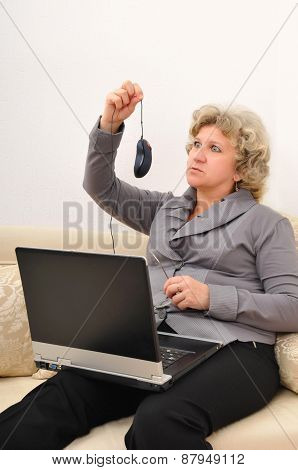 Middle-aged Woman With A Laptop Looking Surptizingly At Computer Mouse