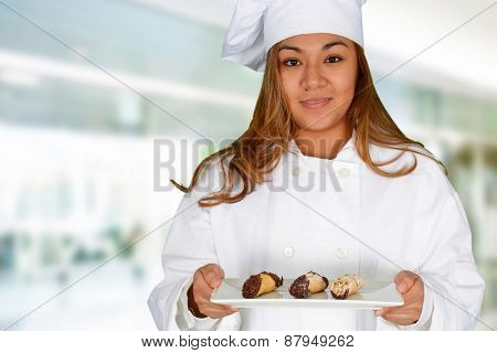 Female cook holding plate with sweet dessert cakes