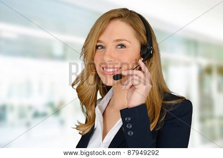 Young blonde blue eyed woman wearing black jacket and talking on headset while smiling to the camera