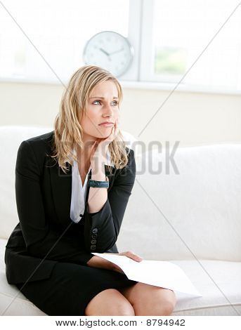 Annoyed Businesswoman Holding A Paper And Sitting On A Sofa