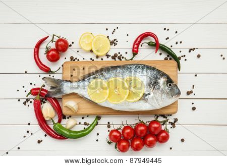 Dorado Fish On Wooden Cutting Board With Cherry Tomatoes