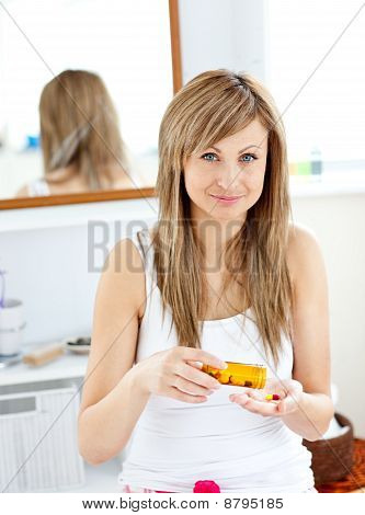 Caucasian Blond Woman Taking Pills Looking At The Camera In The Bathroom