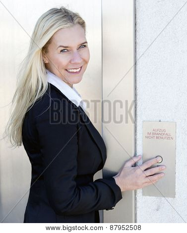 Blond Woman Standing By The Elevator