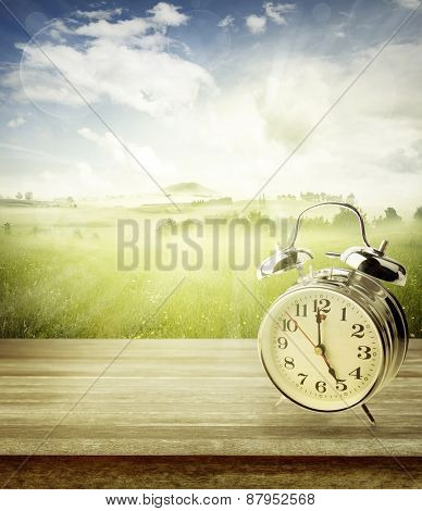 Alarm clock on table in front of spring background. Spring time