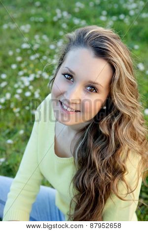 Blonde girl with many daisies around looking at camera