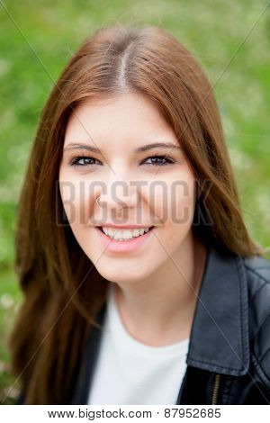 Cool pretty woman relaxed at the park with a leather jacket