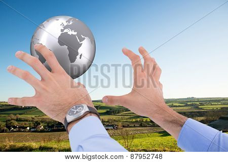 Businessman holding something with his hands against scenic landscape