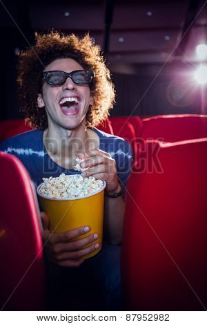 Young man watching a 3d film and eating popcorn at the cinema