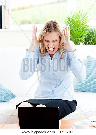 Young Businesswoman Sitting On Her Sofa Getting Frustrated With Her Laptop