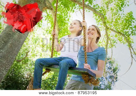 Happy mother swinging daughter at park against heart