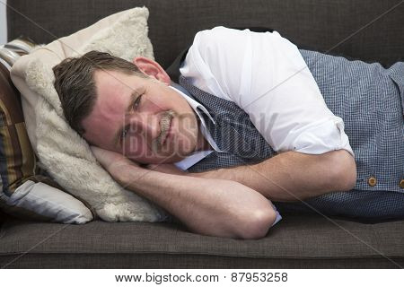 Man Lying On Couch And Smiling