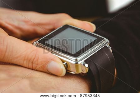 Businesswoman using her smart watch shot in studio