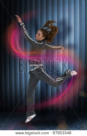 Full length side view of a sporty young blond jumping against dark grey room
