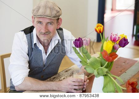Man Sitting At Table With A Glas In His Hands