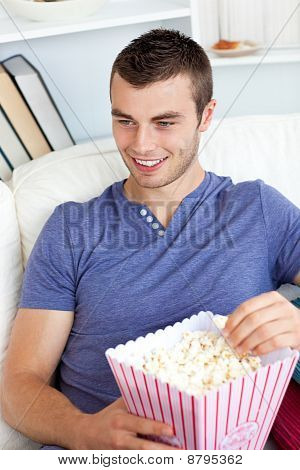 Laughing Caucasian Man Eating Popcorn On A Sofa