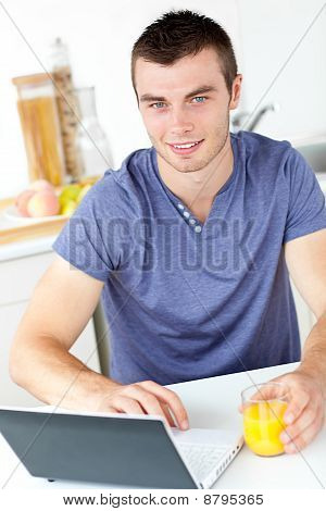 Charming Young Man Using His Laptop Holding Orange Juice In The Kitchen